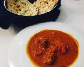British national dish: Home style chicken tikka masala accompanied naan breads