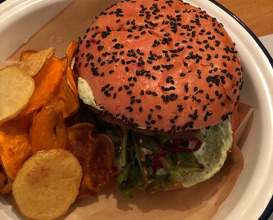 Pink burger bun with beetroot, chickpeas patty, tahini sauce and Bulgarian cheese, root vegetable chips.