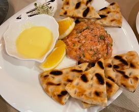 Salmon tartare with wild onion, lemon, olive oil, capers and crispy bruschetta
