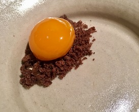 An egg yolk preserved in sugar syrup served on a pile of crumbs made from pine tree bark